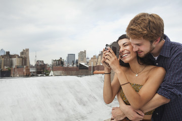 Mixed Race couple hugging on rooftop with video camera