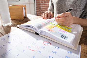 Fototapete - Businesswoman Marking Schedule On Calendar