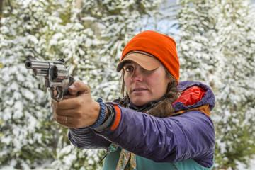 Caucasian woman aiming handgun in winter