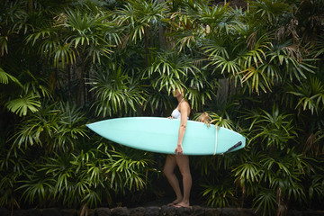 Pacific Islander woman holding surfboard in foliage