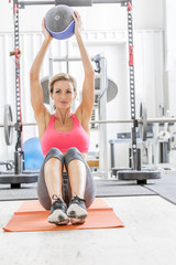 Woman lifting heavy ball on exercise mat in gymnasium
