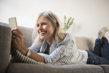 Smiling woman lying on sofa and using smart phone