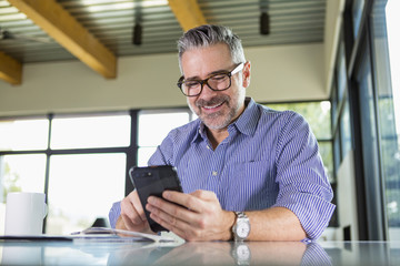 Caucasian man texting on cell phone at table