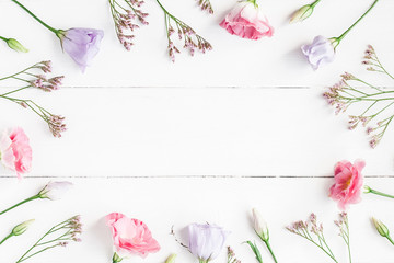 Flowers composition. Frame made of various flowers on white wooden background. Flat lay, top view