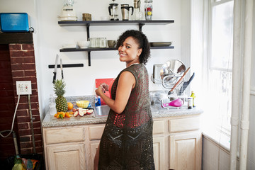 Smiling Mixed Race woman preparing fruit in kitchen