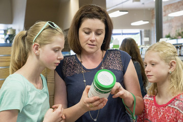 Caucasian mother and daughters reading label in nutrition store