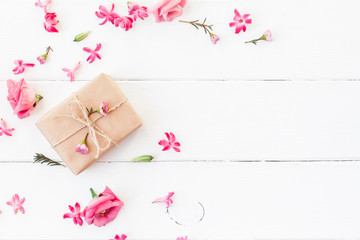 Flowers composition. Gift and pink flowers on white wooden background. Flat lay, top view