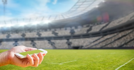 Cropped image of hand holding smart phone at stadium