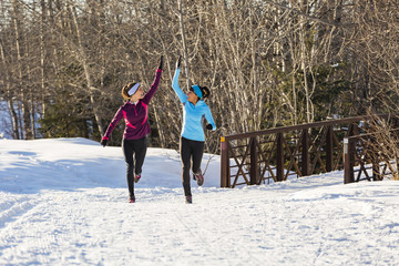 Women running and celebrating on snow in winter
