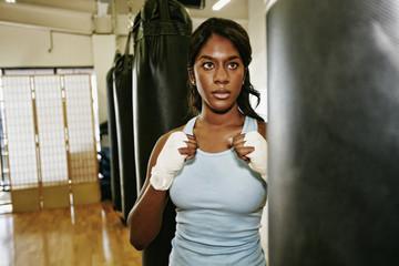 Black woman staring at heavy bag in gymnasium