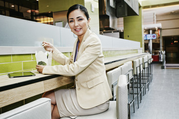 Japanese businesswoman in food court eating food from carton