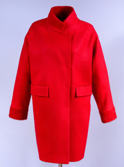 Red stylish coat with pockets isolated on grey background. Outerwear, collection of spring 2017.