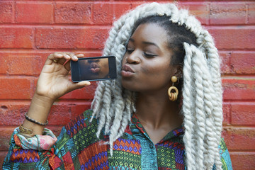 Black woman leaning on brick wall showing photograph of lips
