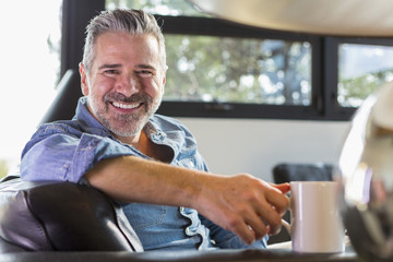 Caucasian man sitting on sofa and drinking coffee