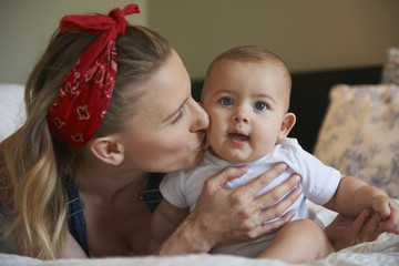 Caucasian mother kissing cheek of baby daughter