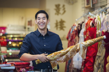 Smiling Chinese man posing with fabric in store