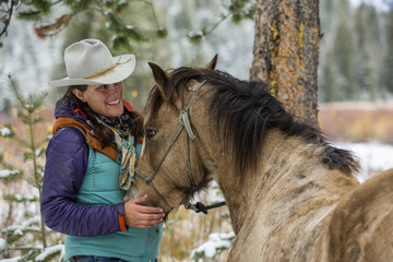 Caucasian woman petting horse in winter