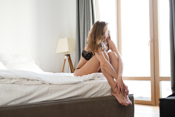 Woman sitting on bed indoors dressed in lingerie.