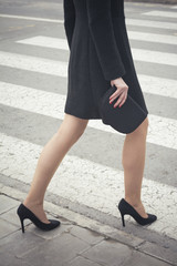 Classic retro styled woman legs portrait - She is over a crosswalk on the street - Fashion classic woman legs