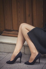 Classic retro styled woman legs portrait - She is sitting in front of a vintage door - Fashion classic woman legs
