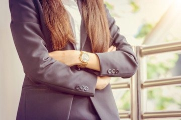 Close up of young business woman standing with arms crossed over blurry background with copy space for concept picture.