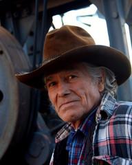 Man wearing cowboy hat looking at camera