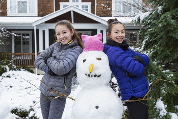 Mixed Race girls posing with snowman wearing pink hat with ears