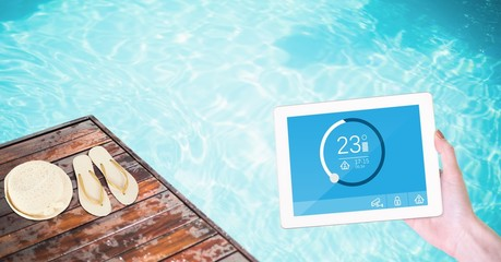 Woman using smart home app on tablet computer by swimming pool