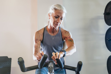 Caucasian woman riding stationary bicycle checking smart watch