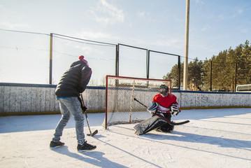 Caucasian boys playing ice hockey outdoors