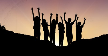 Silhouette children with hands raised on mountain during sunset