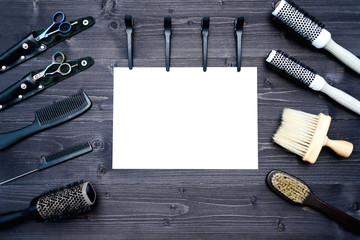 Hairdresser tools on wooden background. Blank card with barber tools flat lay. Top view on wooden table with scissors, comb, hairbrushes and hairclips with empty white paper, free space