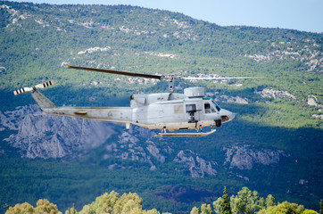 Helicopter bell uh 1. Exhaust gases, machine gun mountain background.