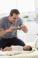 Hispanic father on bed photographing baby daughter with cell phone