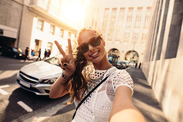 Young woman taking selfie in a street surrounded by buildings.