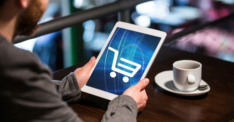 Businessman using tablet PC with shopping cart icon on screen