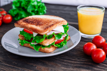 Breakfast sandwich and orange juice, tomatoes on the wooden table top view