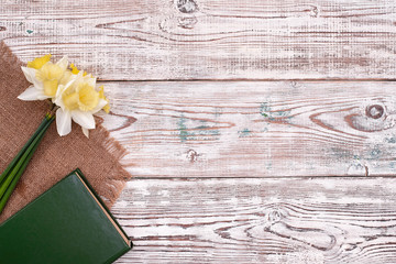 book with flower on vintage wooden table background top view