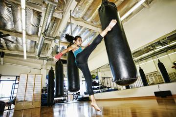 Asian woman kicking heavy bag in gymnasium