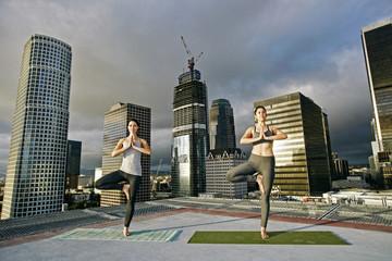 Caucasian women doing yoga urban rooftop