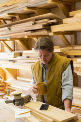 Caucasian carpenter drinking coffee and using cell phone in workshop