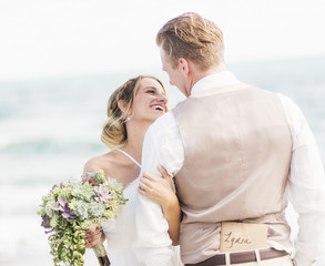Caucasian bride and groom hugging on beach