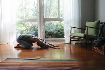 Caucasian woman kneeling on floor stretching