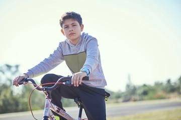 Serious Hispanic boy posing on bicycle