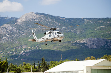 Black hawk helicopter rescue team.exhaust gas, approach landing,mountain background
