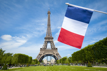 French flag flying in front of the Eiffel Tower on a bright summer day