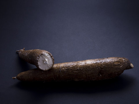 Fresh, raw manioc, also called cassava or yucca root, isolated on black background