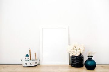 Front view blank mock up of photo frame with trendy stuff at white background. Minimalistic decorated home office concept.