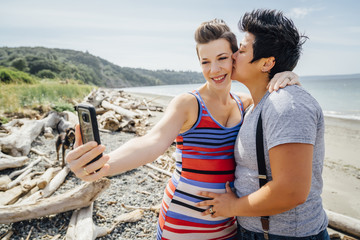 Pregnant lesbian couple posing for cell phone selfie on beach