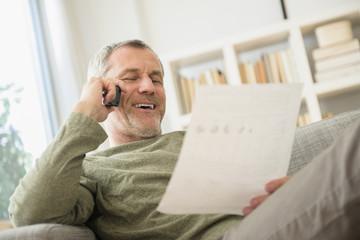 Older Caucasian man talking on telephone reading paperwork